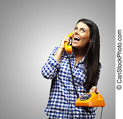 portrait of young woman talking on vintage telephone over grey