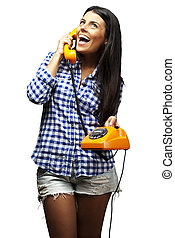 portrait of young woman talking on vintage telephone over white
