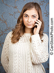 portrait of young woman talking using a telephone against a vintage background