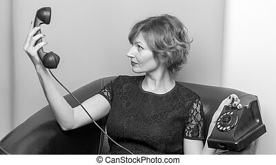 Portrait of young woman talking using a vintage telephone agains