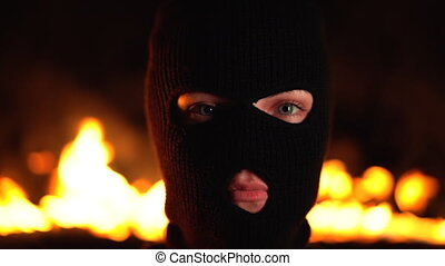 Portrait of young woman ultras or protester in black mask...