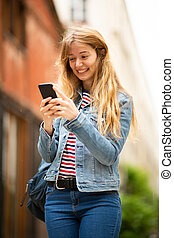 young woman walking outside looking at cellphone