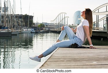 Portrait of young woman which is relaxing at pier
