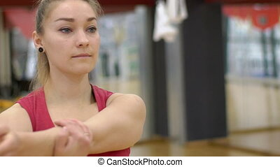 Portrait of young woman, who is warming up her muscules before training in modern gym, slow motion.