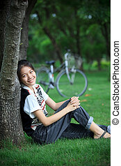 portrait of young woman with blur biclycle background relaxing i