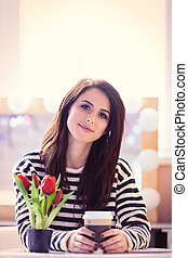 portrait of young woman with bunch of tulips and cup of coffee