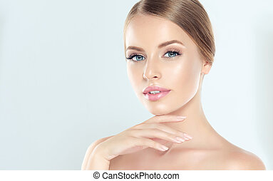 Young blond-haired woman with clean fresh skin and soft, delicate make up. Woman is touching tenderly own face. Image of freshness and cleanliness. Cosmetology, plastic surgery, facial treatment and beauty technologies.