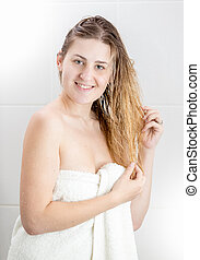 Portrait of young woman with long blond hair looking in camera after having shower