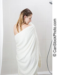 Portrait of young woman with long hair covering in towel after bathing