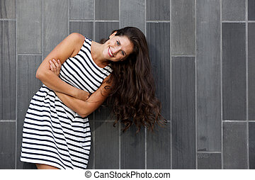 young woman with long hair laughing against gray background