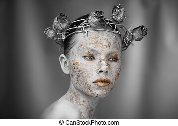 Portrait of young woman with marble skin and wearing a wreath of barbed wire and dry roses.