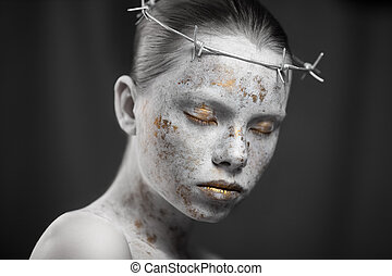 Portrait of young woman with marbled skin in a wreath of barbed wire.