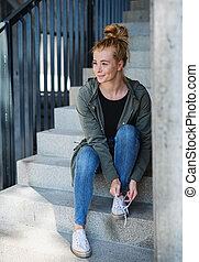 Portrait of young woman with red hair outdoors in town, tying shoelaces on staircase.