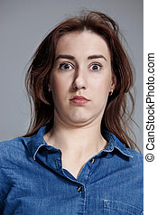 Portrait of young woman with shocked facial expression - ...