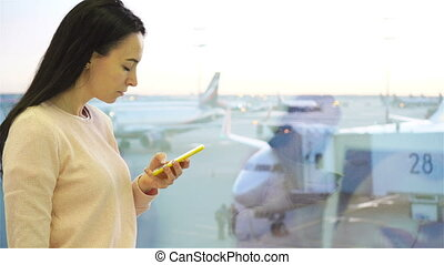 Portrait of young woman with smartphone in international airport. Airline passenger in an airport lounge waiting for flight aircraft