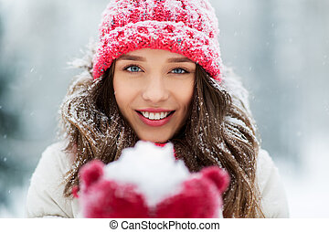 portrait of young woman with snow in winter park