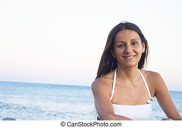 Portrait of young woman with sunset on the beach