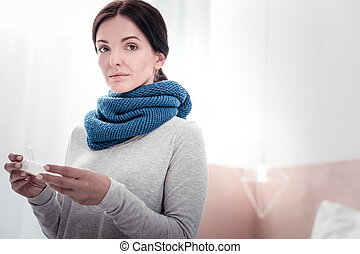 Portrait of young woman with the scarf and vitamins box
