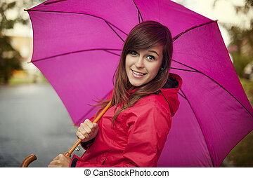 Portrait of young woman with umbrella