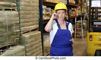 Portrait of young woman worker in uniform speak by mobile in build store