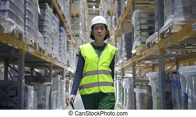 Portrait of young woman worker walking on warehouse during working day at factory.
