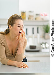 Portrait of young woman yawning in kitchen