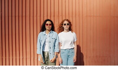 Portrait of young women standing outdoors looking at camera ...