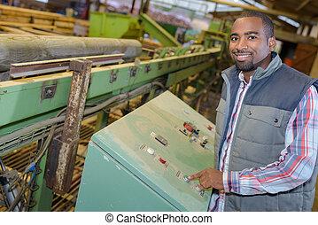 Portrait ofworker operating machine in wood yard