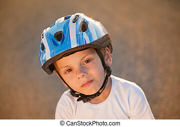 portrait or cute small child in sport helmet standing on abandoned road in warm summer sunset