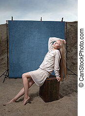 portrait outdoors on sand in front of blue studio backdrop, pretty female posing