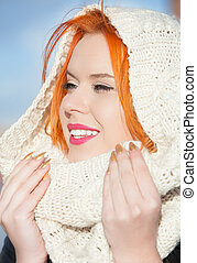 Portrait red haired happy girl in warm white scarf outdoor