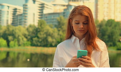 portrait redhead girl holding smartphone - young caucasian...