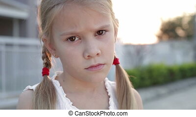 Portrait sad little girl standing near a house