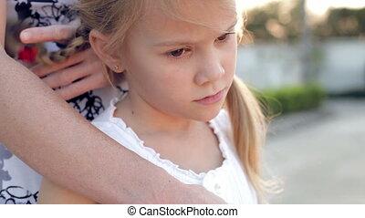 Portrait sad little girl standing near the house
