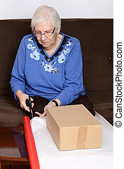 senior woman cutting christmas pape