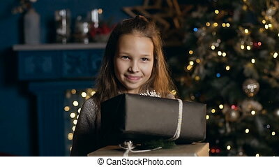 Portrait shot of beatiful girl holding two present and smiling on camera in the room with christmas tree.