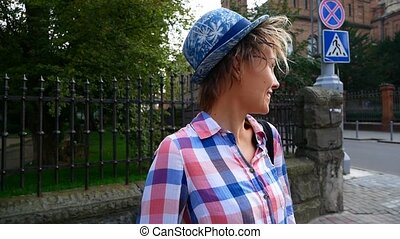 Portrait shot of beautiful young woman in hat in the old city.