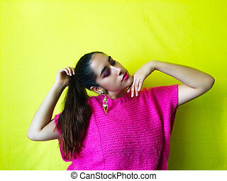Portrait shot of stylish pretty young woman with pink lips and bright pink outfit against colorful background in vibrant yellow.