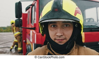Portrait shot of the fireman in full uniform ready for the rescue. Slow motion.