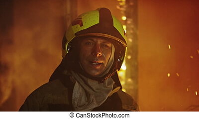 Portrait shot of tired firefighter in front of the burning house. Slow motion
