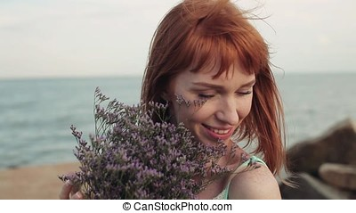 Portrait. Slow motion. Beautiful sexy girl poses positively with flowers at the sea