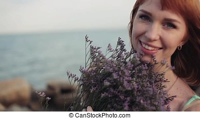 Portrait. Slow-motion shooting. Beautiful sexy girl with a bouquet of flowers in sunny weather beautifully smiles against the sea