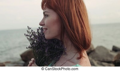 Portrait. Slow motion. Young sexy girl with bouquet of flowers on the sea