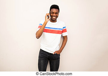 smiling african american man standing by white wall talking with mobile phone
