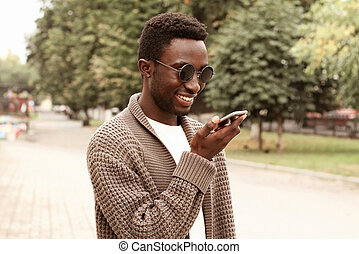 Portrait smiling african man with smartphone using voice command recorder, assistant or takes calling in city park