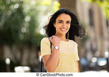 smiling beautiful young hispanic woman outdoor
