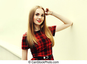Portrait smiling blonde young woman with red lips wearing dress over wall background