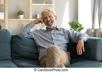Portrait smiling mature man sitting on couch at home - ...