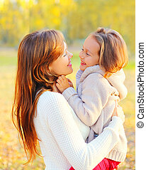 Portrait smiling mother hugging child in warm sunny autumn day