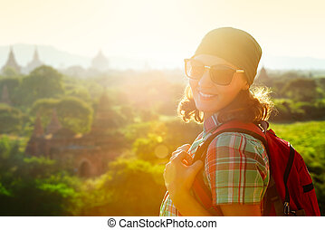 Portrait smiling of traveler girl with backpack on the background of sunset. Focus on traveller
